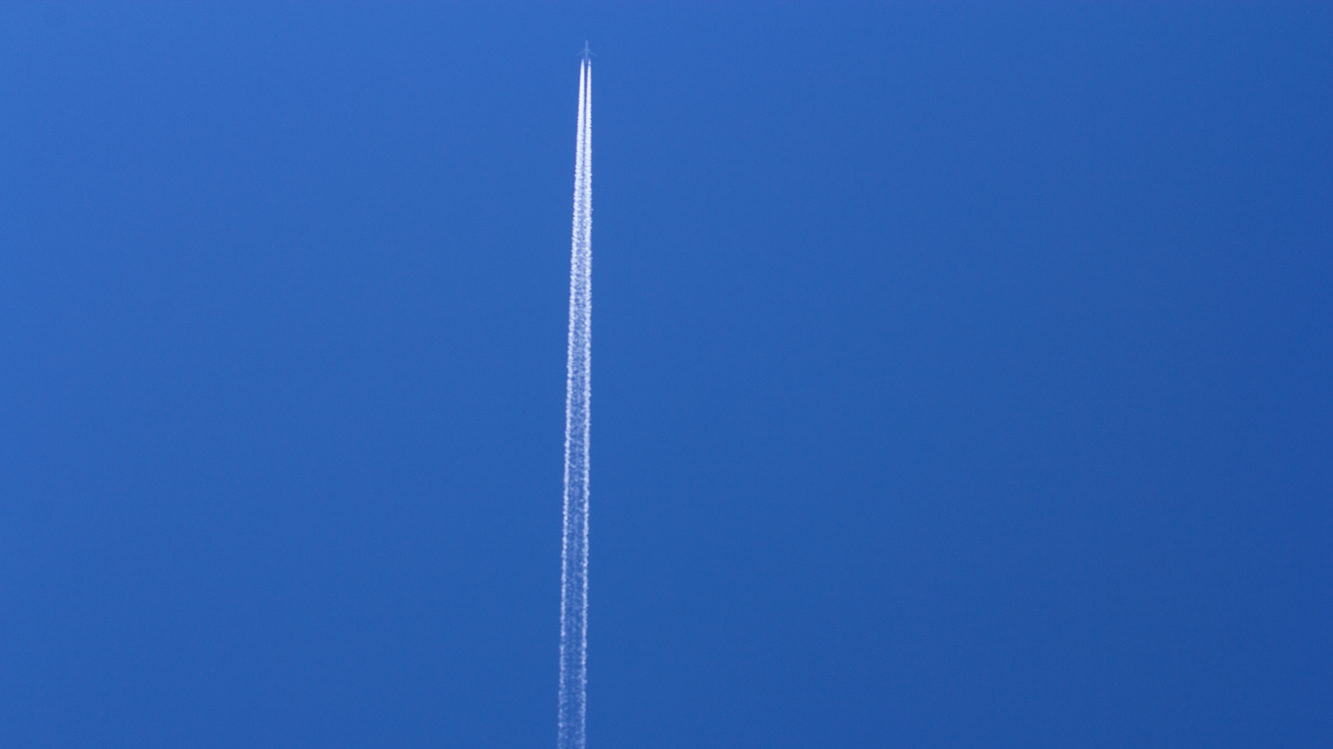 Airplane making white streaks on blue sky